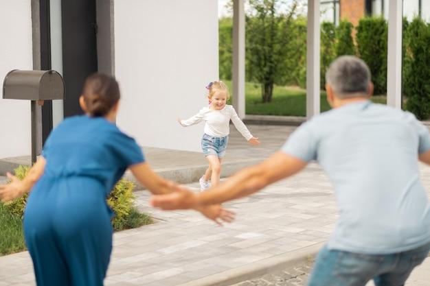 Bieganie do rodziców. blondwłosa śliczna mała dziewczynka uśmiecha się biegnąc do rodziców