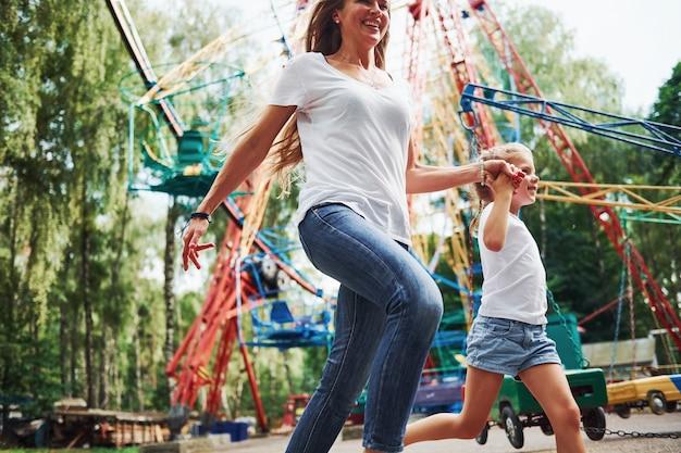 Bieganie i granie. wesoła dziewczynka jej mama dobrze się bawi w parku w pobliżu atrakcji.