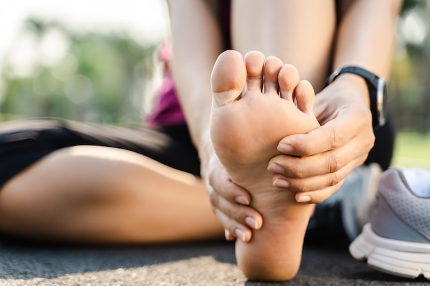 Bieganie kontuzji nogi wypadek - sport kobieta biegacz boli trzymając bolesne skręconą kostkę w bólu. lekkoatletka z bólem stawów lub mięśni i problemami z bólem dolnej części ciała.