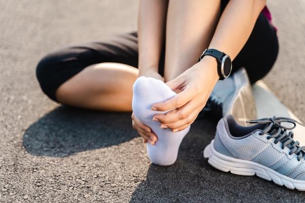 Bieganie kontuzji nogi wypadek - sportowa kobieta biegaczka boli, trzymając bolesną skręconą kostkę w bólu. lekkoatletka z bolesnością stawów lub mięśni i problemami z bólem dolnej części ciała.