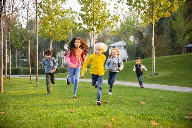 Bieganie. międzyrasowa grupa dzieci, dziewcząt i chłopców grających razem w parku w letni dzień. przyjaźń nie ma rasy. szczęście, dzieciństwo, edukacja, koncepcja różnorodności. wyglądaj na szczęśliwego i szczerego.