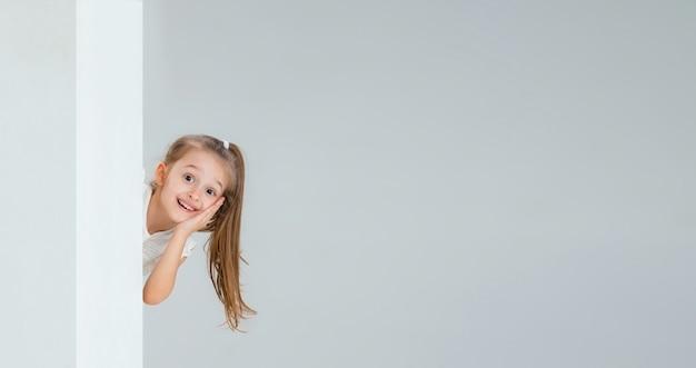 Bieganie, skakanie, zabawa. portret całkiem kaukaski dziewczyna na białym tle na białej ścianie z copyspace. pojęcie ludzkich emocji, młodości, dzieciństwa, edukacji, sprzedaży, wyrazu twarzy.