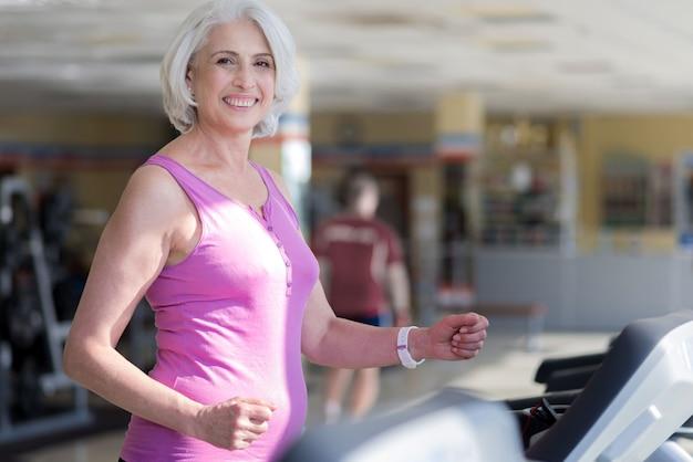 Bieganie to moje hobby. pozytywny piękny starszy kobieta bieganie na bieżni i uśmiechnięty podczas ćwiczeń na siłowni.