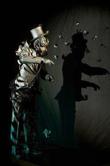 Biegły aktor mim, który wygląda jak posąg stojący nad czarną ścianą w tle ze swoim cieniem. koncepcja spektakularnego aktu pantomimy