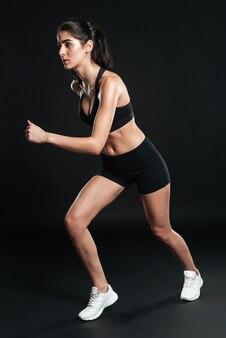 Biegnąca kobieta na całej długości po czarnej ścianie