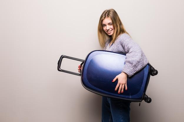 Biegnąca kobieta z walizką. piękna dziewczyna w ruchu. podróżny z bagażem na białym tle. podróżująca nastolatka