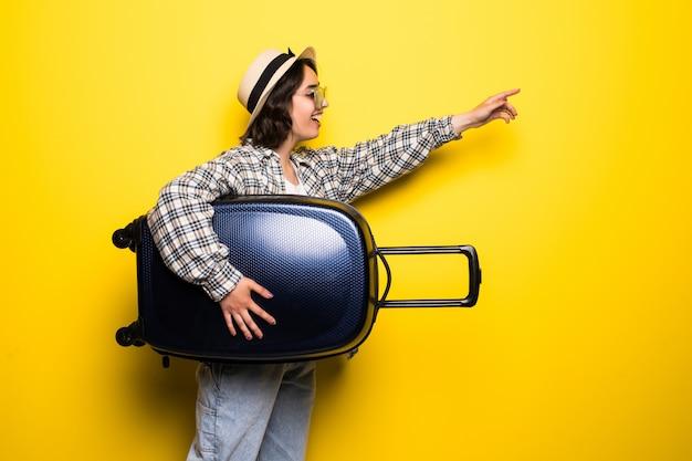 Biegnąca kobieta z walizką wskazał rękami. piękna dziewczyna w ruchu. podróżny z bagażem na białym tle.