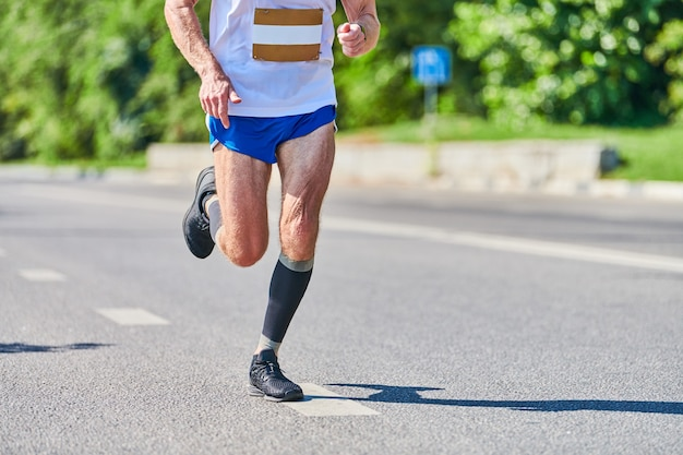 Biegnący mężczyzna. lekkoatletycznego mężczyzna joggingu w odzieży sportowej na drodze miasta.