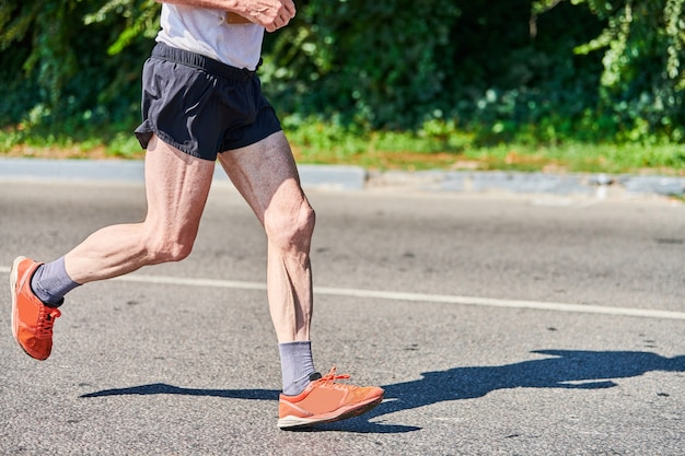 Biegnący stary człowiek. stary człowiek joggingu w odzieży sportowej na drodze miasta