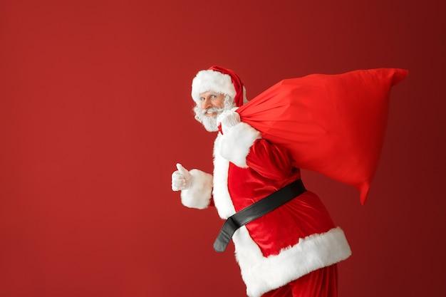 Biegnący święty mikołaj z torbą pełną prezentów w kolorze