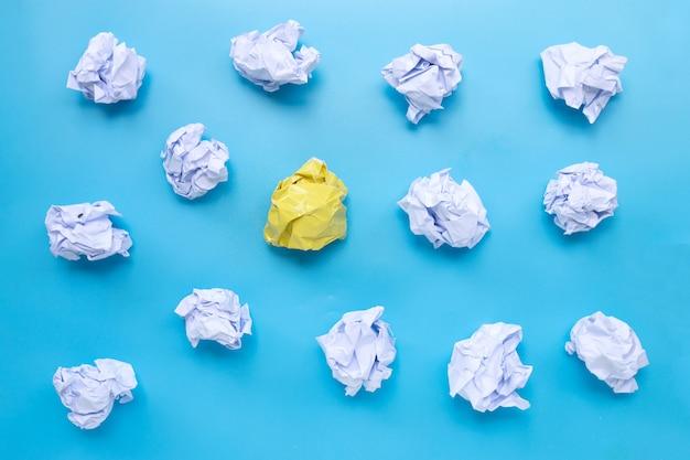 Biel z żółtymi zmiętymi papierowymi piłkami na błękitnym tle.