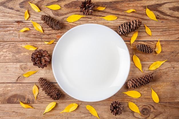 Bielu talerz otaczający sosnowymi rożkami i małymi żółtymi liśćmi na drewnianym tle