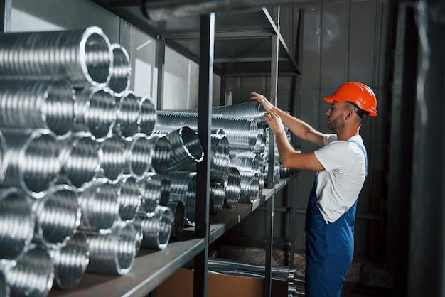 Bierze jedną z rur wentylacyjnych. mężczyzna w mundurze pracuje nad produkcją. nowoczesna technologia przemysłowa.