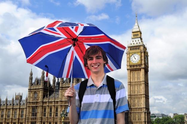 Big ben i turystyczny z brytyjskiej flagi parasolem w londynie