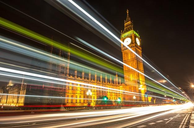 Big ben, jeden z najbardziej znanych symboli zarówno londynu, jak i anglii, pokazany nocą wraz ze światłami przejeżdżających samochodów