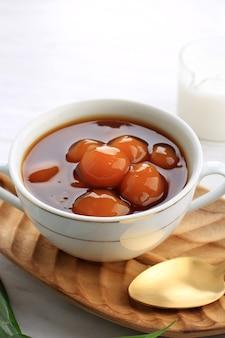 Biji salak kabocha (lub candil) to słynny indonezyjski deser podczas śniadania podczas ramadanu. wykonane z kulek kabocha ze słodkich ziemniaków lub żółtej dyni z syropem z cukru palmowego i mlekiem kokosowym. wybrany fokus