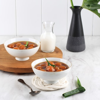 Biji salak kabocha (lub candil) to słynny indonezyjski deser podczas śniadania podczas ramadanu. wykonane z kulek kabocha ze słodkich ziemniaków lub żółtej dyni z syropem z cukru palmowego i mlekiem kokosowym.