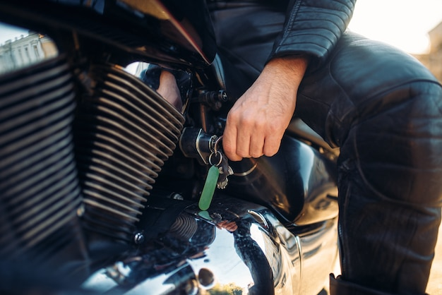 Biker wkłada kluczyk do stacyjki klasycznego choppera.