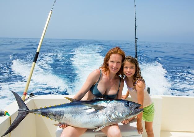 Bikini fisher kobieta i córka z tuńczykiem błękitnopłetwym