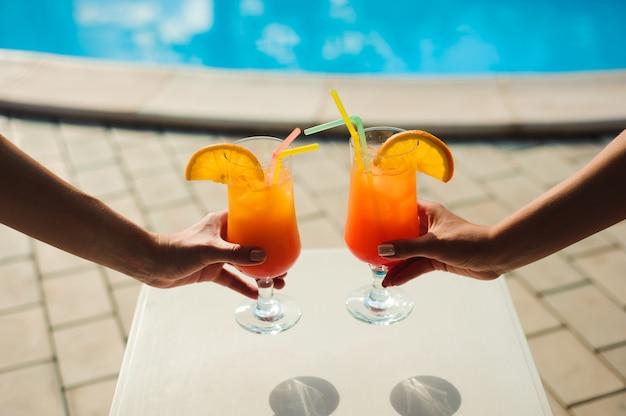 Bikini kobiety w basenie relaksuje z sokiem, młode piękne seksowne dziewczyny odpoczywa w wakacje w sezonie letnim przy pływackim basenem.