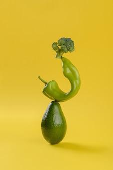 Bilans żywności świeżych zielonych warzyw na żółtym tle, awokado, pieprz i brokuły dieta wegetariańska i wegańska równoważenie koncepcji kreatywnej żywności, miejsce, zdrowa dieta alkakina