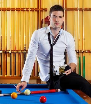 Bilardowy przystojny gracza mężczyzna pije alkohol