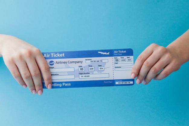Bilet lotniczy w kobiecej dłoni na różu
