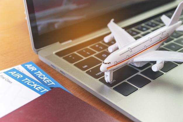 Bilety lotnicze i paszporty w pobliżu laptopa i samolotu na stole. koncepcja rezerwacji biletów online