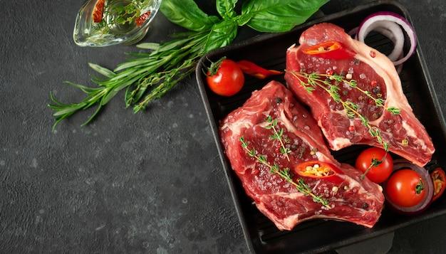 Bili cielęcy na patelni grillowej z warzywami, ziołami i oliwą. gotowanie mięsa. widok z góry, miejsce na kopię.