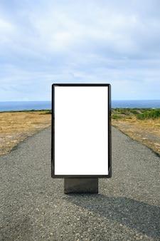Billboard plakatowy na drodze do latarni morskiej. makieta pustego billboardu reklamowego na ulicy