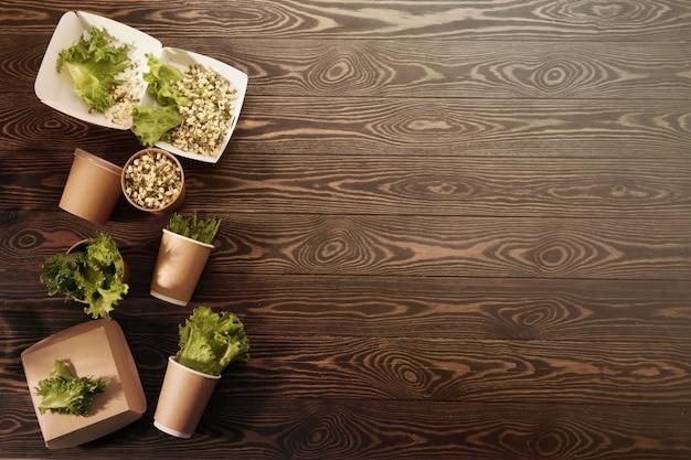 Biodegradowalna zastawa stołowa i warzywa na powierzchni drewnianej