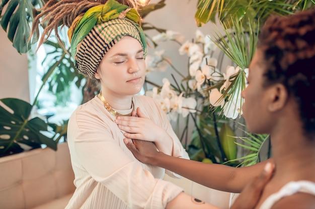 Bioenergia. ciemnoskóra i kaukaska młoda dorosła kobieta z zamkniętymi oczami siedzi naprzeciwko siebie dotykając dłoni medytując w salonie spa