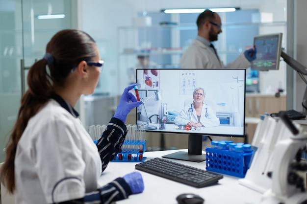 Biolog badaczka kobieta trzymająca w rękach probówkę do badania krwi, omawiająca szczepionkę medyczną