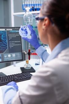 Biolog kobieta patrząca na wirus bakterii za pomocą medycznej szalki petriego