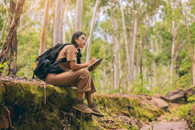Biolog lub botanik rejestrujący informacje o małych roślinach tropikalnych w lesie