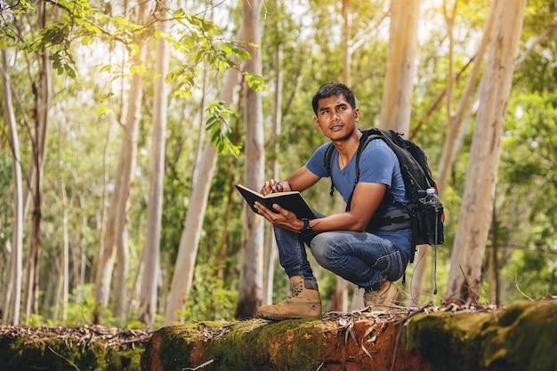 Biolog lub botanik rejestrujący informacje o roślinach tropikalnych w lesie