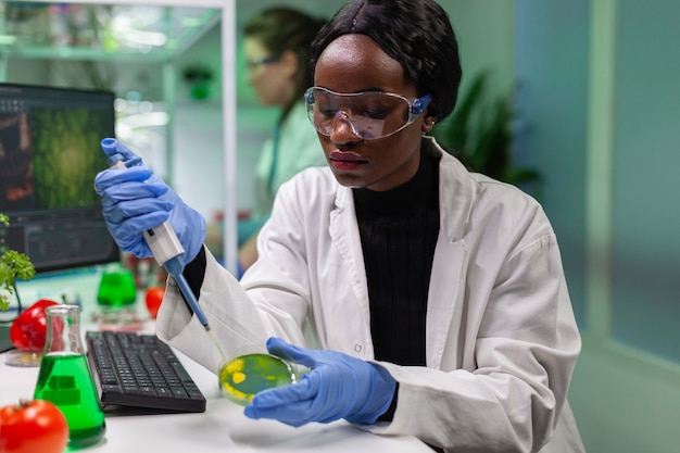 Biolog naukowiec afrykańska kobieta badaczka pobierająca roztwór genetyczny z probówki