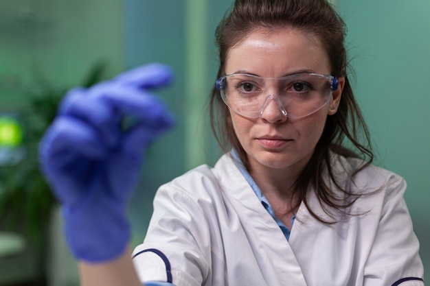 Biolog naukowiec patrzący na próbkę badaną za pomocą mikroskopu w celu uzyskania wiedzy chemicznej. chemik naukowiec kobieta pracująca w laboratorium farmaceutycznym odkrywająca mutację genetyczną roślin.