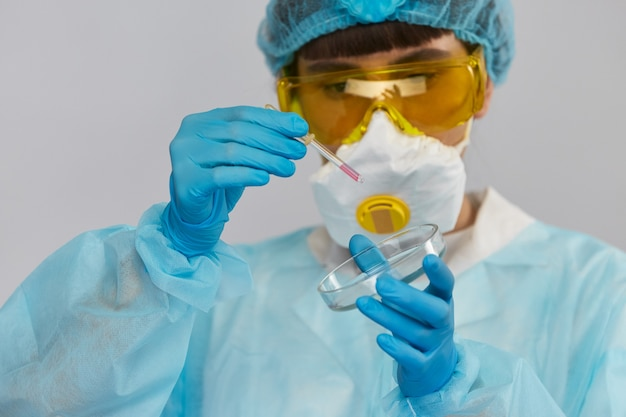 Biolożka w kombinezonie ochronnym i okularach pozostawiająca próbki pipetą