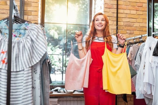 Biorąc dwa. podekscytowana młoda kobieta wyglądająca na szczęśliwą i uśmiechniętą, odwiedzając ładny sklep i kupując dwie cudowne bluzki