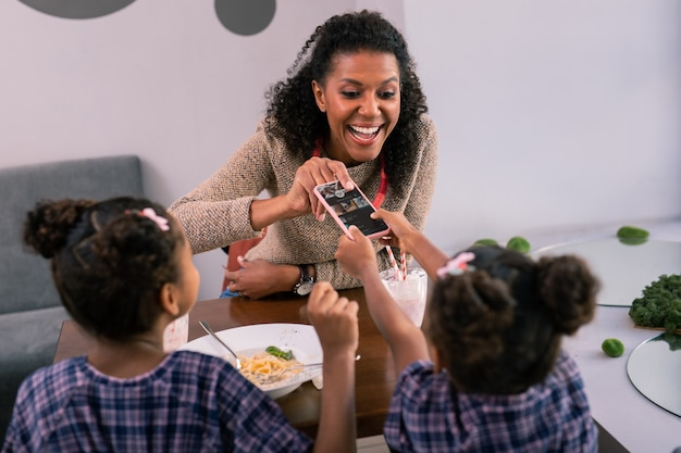 Biorąc smartfon. kędzierzawa ciemnowłosa mama ubrana w sweter, która bierze smartfona od córeczki