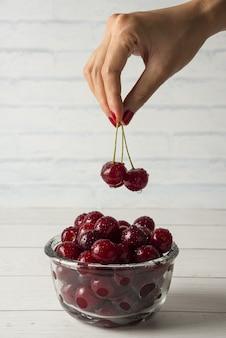 Biorąc wiśnie z miski szklanej na białym tle