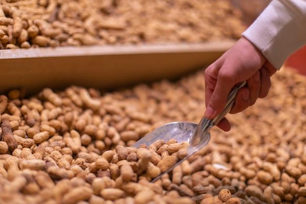 Biorę orzeszki ziemne z zapasów w sklepie spożywczym. wysokiej jakości zdjęcie