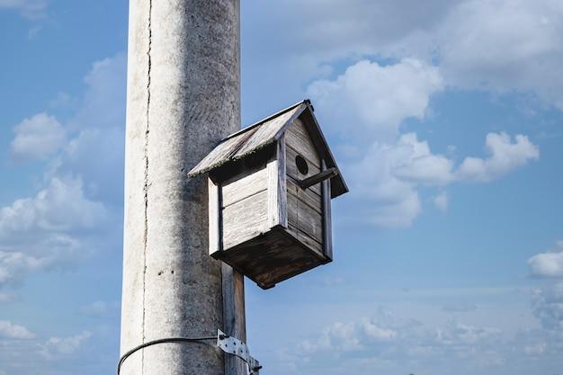 Birdhouse dla ptaków na betonowym słupie w centrum miasta na tle błękitnego nieba. opieka nad ptakami w dużym mieście.