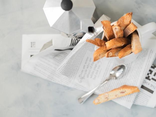 Biscotti (cantuccini) - tradycyjny włoski deser migdałowy z dzbankiem do kawy moka na gazecie.