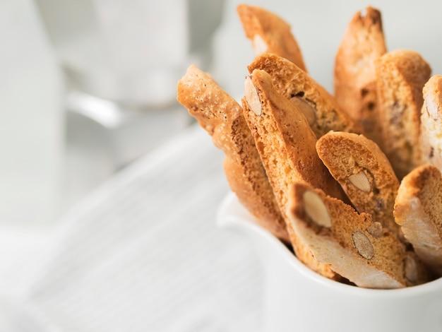 Biscotti (cantuccini) - tradycyjny włoski migdałowy deser w białym filiżanki zbliżeniu.