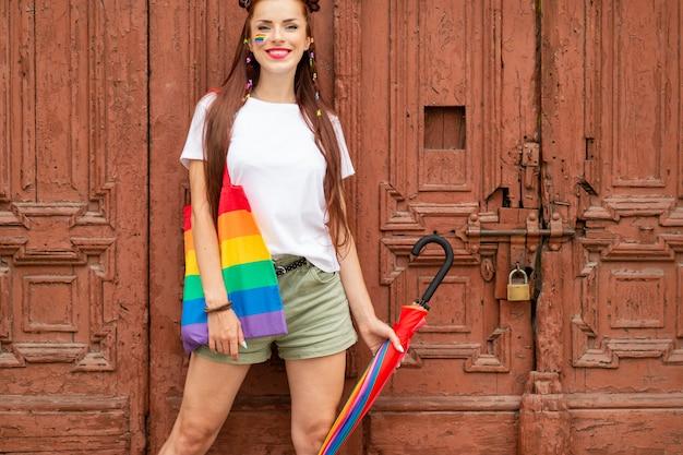 Biseksualna dziewczyna w kolorowych ubraniach pozuje nad starymi drzwi