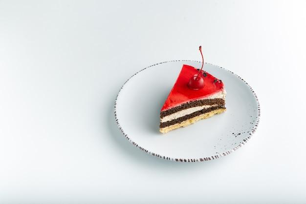 Biszkopt z czerwonym polewą i wiśnią maraschino na białym talerzu.