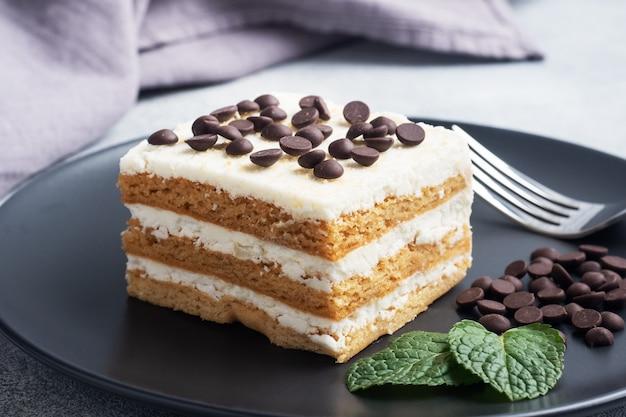 Biszkopt z kremem i kawałkami czekolady miętowej na czarnym talerzu. deser na uroczystość lub przyjęcie urodzinowe.