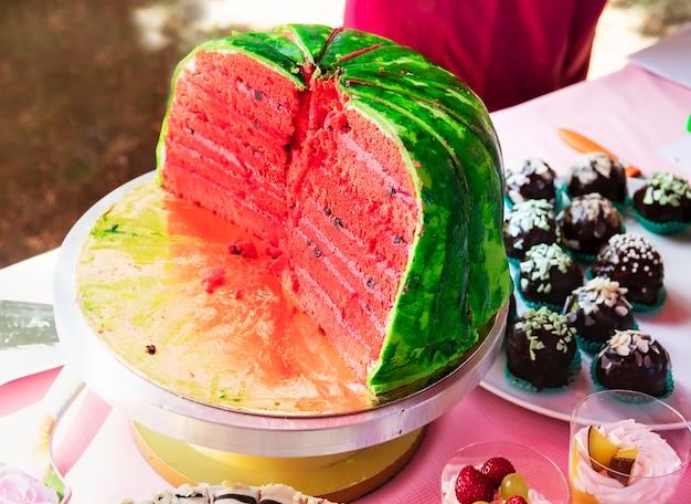 Biszkopt z kremem w kształcie arbuza na tortownicy i ciasta z owocami